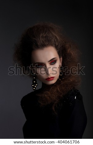 Fashionable woman with high hair, a photo session in the studio. Red lips, professional makeup. - stock photo