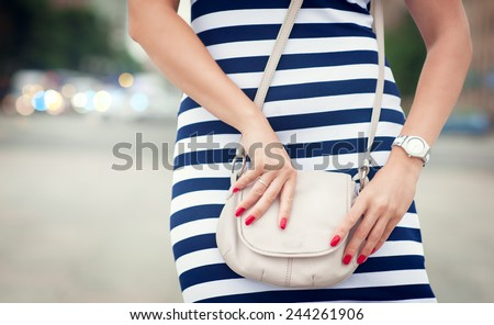 Fashionable woman with white bag in her hands and striped dress in the city - stock photo