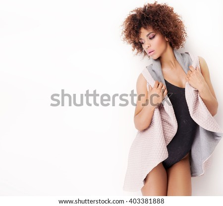 Fashionable young african american girl posing in studio. Woman with afro. Slim body.