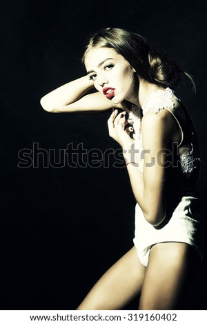 Fashionable young attractive woman posing with long lush hair and red lips in stylish short cocktail white overalls from lace standing with raised hand in studio on black background, vertical picture - stock photo