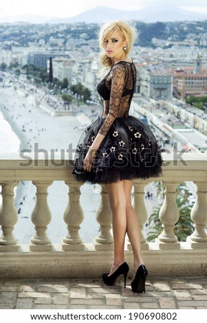 Fashionable young beautiful woman posing in elegant dress. Outdoor shot. Full body. Blonde sensual lady. - stock photo