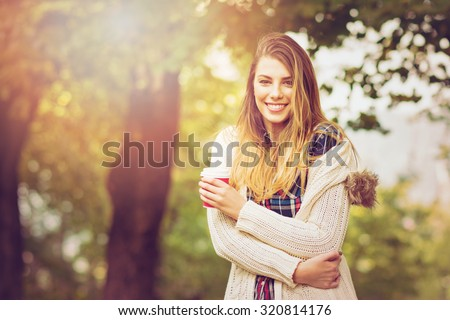 Fashionable young blonde woman in autumn in park smiling wearing beige sweater holding a cup of takeaway coffee. Horizontal, retouched, vibrant colors, filter applied. - stock photo