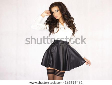 Fashionable young brunette woman posing wearing leather skirt and white shirt, looking at camera. - stock photo