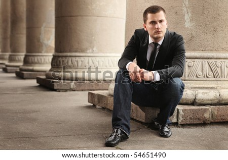 fashionable young businessman sitting on the base of column - stock photo