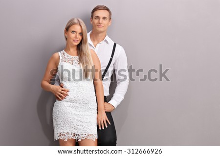 Fashionable young couple in stylish clothes posing together in front of a gray wall - stock photo