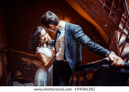 Fashionable young couple standing on stairs and hugging each other  - stock photo