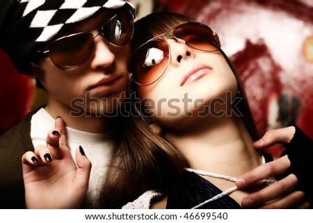 Fashionable young couple wearing sunglasses