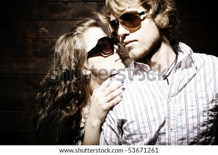Fashionable young couple wearing sunglasses isolated on grunge background