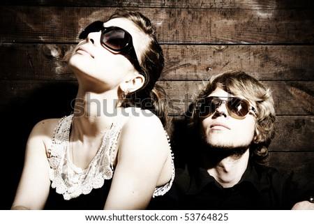 Fashionable young couple wearing sunglasses isolated on grunge background - stock photo