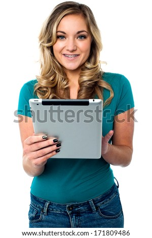 Fashionable young female operating her tablet pc - stock photo
