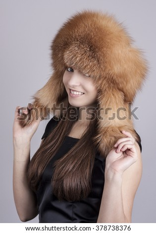 Fashionable young girl in a hat. Hat fur fox.