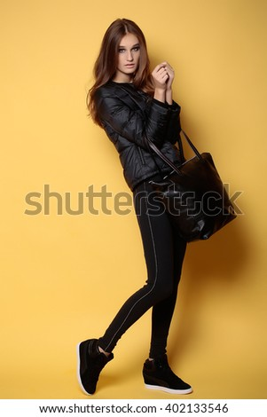 Fashionable young girl in black sport cloth holding leather handbag on yellow background