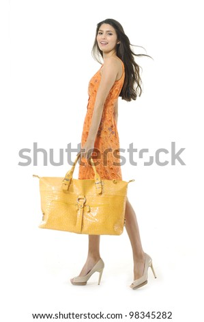 Fashionable young girl with a handbag walking on white background - stock photo