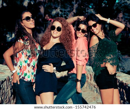 Fashionable young girls with sunglasses. outdoors shot. horizontal - stock photo
