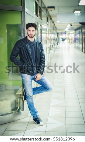 fashionable young man in a leather jacket walking by night through the empty shopping center
