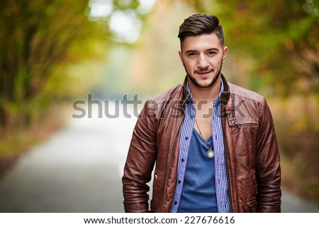 Fashionable young man in leather jacket outdoor in a forest - stock photo