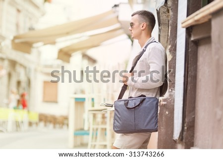 Fashionable young man leaning on the wall on the city street waiting public transportation