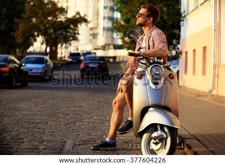 fashionable young man riding a vintage scooter in the street