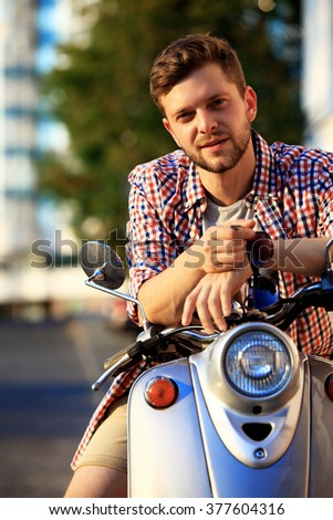 fashionable young man riding a vintage scooter in the street  - stock photo