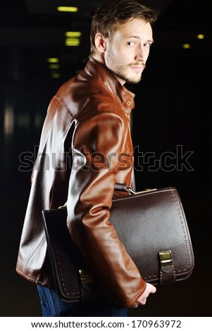 Fashionable young man with leather clothes on - stock photo
