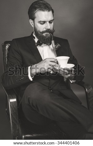 Fashionable young man with retro look sitting in an armchair, smoking pipe and holding a cup of coffee over gray background
