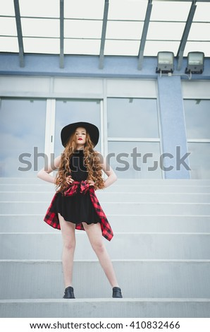 Fashionable young redhead woman posing on stairs