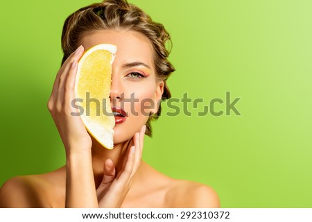 Fashionable young woman holding papaya over green background. Tropical fruits.  Healthy eating. Beauty, cosmetics. - stock photo