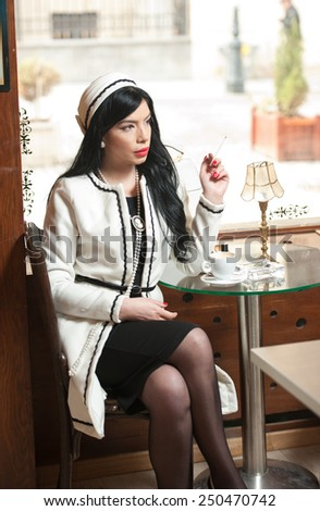 Fashionable young woman in black and white outfit drinking coffee in restaurant. Beautiful brunette in elegant scenery with a cup of coffee on the table. Attractive lady with coat in coffee shop - stock photo