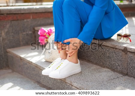 Fashionable young woman in blue suit and white sneakers on the city streets. Fashion. Backpack. Shawl. - stock photo