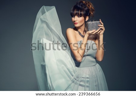 fashionable young woman in elegant dress holding evening handbag. Glamour style - stock photo