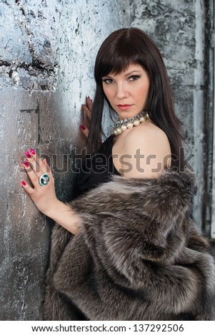 Fashionable young woman in fur coat posing by the wall and looking at camera, vertical shot - stock photo