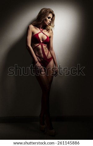 Fashionable young woman in red swimsuit with long curly hair. Bblonde posing in studio on black background - stock photo