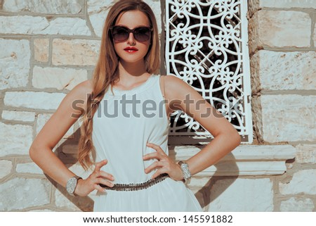 fashionable young woman in summer dress and sunglasses posing against old stone wall. soft sunny colors. outdoors horizontal shot. - stock photo