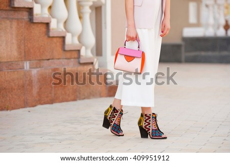 Fashionable young woman in white clothes with a handbag on the city streets . - stock photo