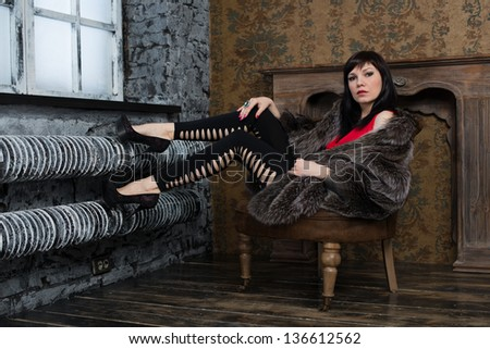 Fashionable young woman posing in a vintage interior, studio shot - stock photo