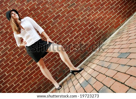Fashionable young woman posing in front of a brick wall. - stock photo