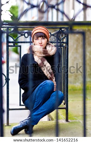 fashionable young woman sitting and looking straight to the camera - stock photo