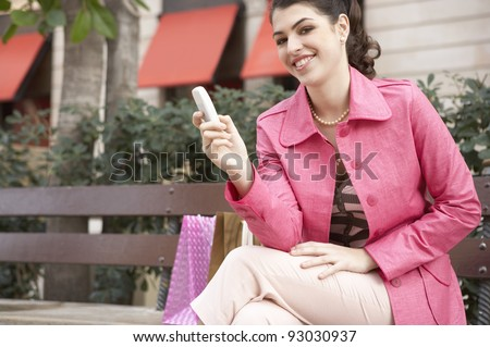Fashionable young woman sitting down on a bench in a shopping street. - stock photo