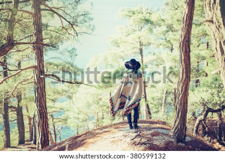 Fashionable young woman wearing in hat and poncho standing on coast in the forest among pine trees and looking at sea, rear view