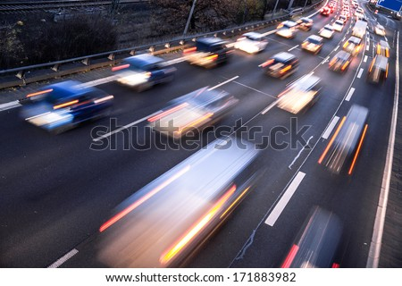 fast cars on highway in evening light - stock photo