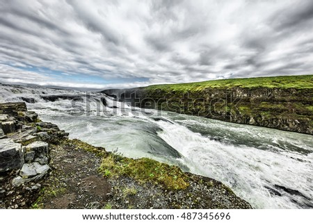 Fast cascade river and low clouds in Iceland