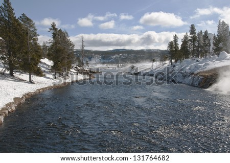 Fast flowing river in Yellowstone National Park. Note the heard of bison (buffalo) on the left side of the river - stock photo