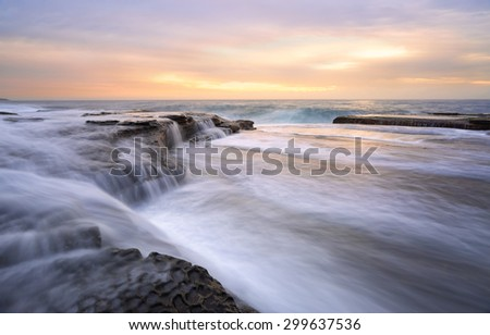 Fast flowing torrents at Curl Curl rock shelf.   One large waves flows off the rocks like a waterfall as the swell builds another wave.   These fast flowing waters feel like whitewater  river flows - stock photo