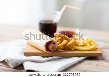 fast food and unhealthy eating concept - close up of deep-fried squid rings, french fries, drink and ketchup on wooden table - stock photo