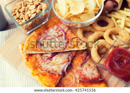 fast food and unhealthy eating concept - close up of pizza and other snacks on wooden table