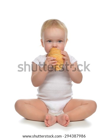 Fast food concept. Infant child baby toddler hold bread croissant in hands hungry getting ready to eat isolated on a white background - stock photo