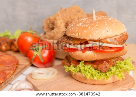 Fast food concept with burger , fried chicken , pizza as a symbol of diet temptation resulting in unhealthy nutrition - stock photo