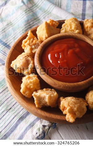 Fast food: crispy popcorn chicken fillet with sauce close-up on a plate. Vertical - stock photo