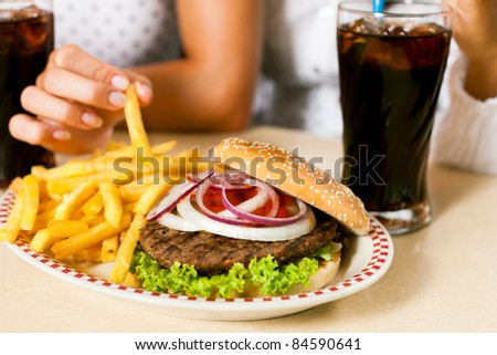 Fast food hamburger and fries in a restaurant on a dish - close-up and focus on the burger - stock photo