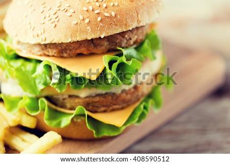 fast food, junk-food and unhealthy eating concept - close up of hamburger or cheeseburger on table - stock photo